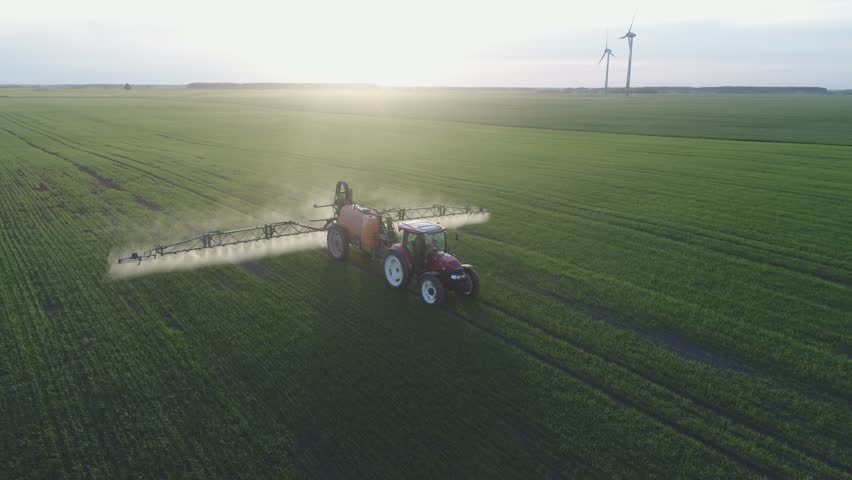 4K aerial view. Tractor is spraying pesticides on grain field. | Shutterstock HD Video #28015870