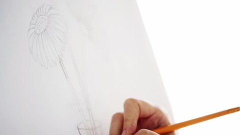art, creativity and people concept - artist hand with graphite pencil drawing still life picture of flower in vase on paper