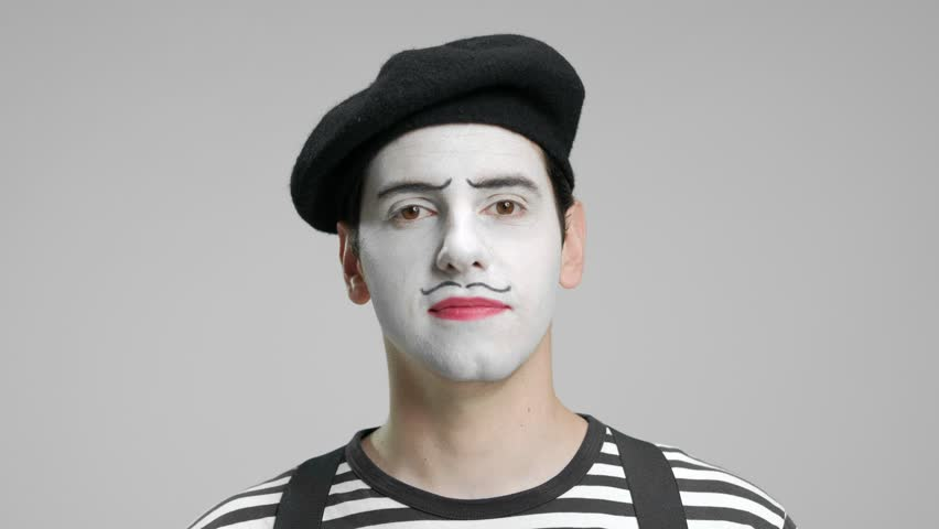 Close-up of a mime looking at the camera and smiling isolated on gray background