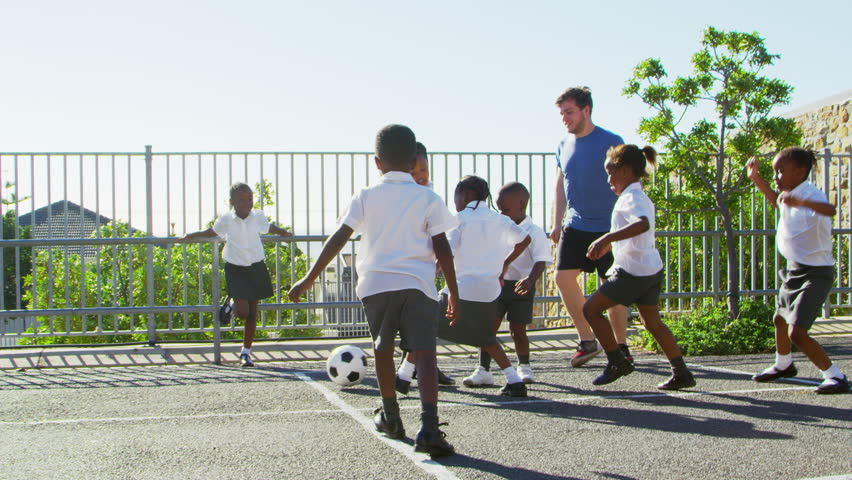 Teacher plays football with young kids in school playground
