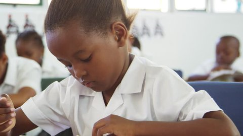 Schoolgirl turning page in a book in elementary school class