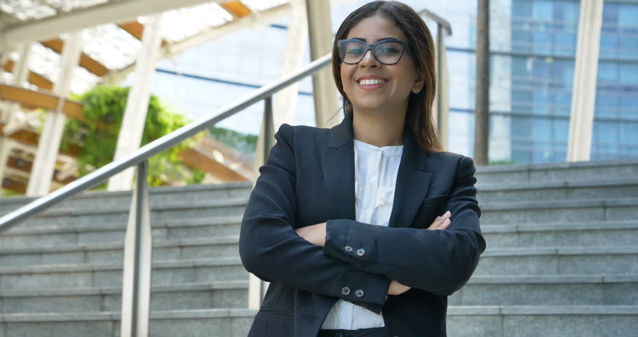 Portrait of young beautiful business woman (student) in suit, glasses, smiling, happy, walking down stairs, steps, on building background. Concept: new business, communication, Arab, banker, manager. | Shutterstock HD Video #28051642