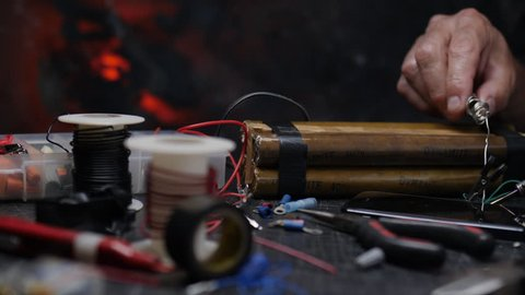 BOMB MAKING.  Slow, close up, dolly shot of a pair of male hands soldering an electrical connection for a bomb.  Shot in 4K, 10 bit.