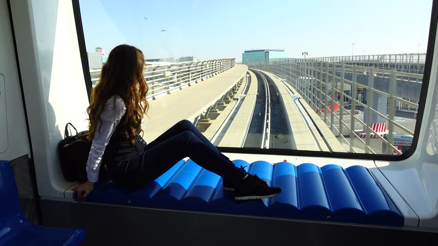 Young adult woman sit against front window at inter-terminal train, look outside. Leonardo da Vinci airport connection between buildings, international arrival passage. Sunny day outdoors