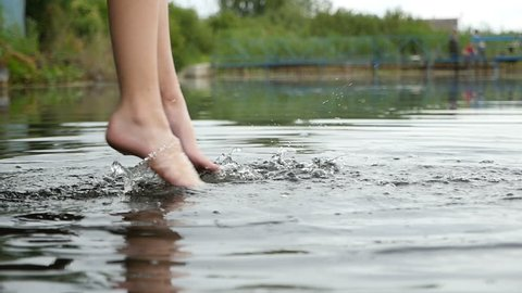 Impressive closeup  of frolicking female legs with a fashionable makeup, which are swinging, while touching water in a lake in a relaxed way. The young woman is sitting on a wooden bridge in slo-mo