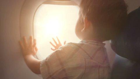 Little boy looking outside of airplane window