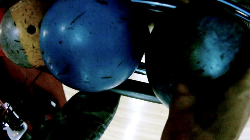 Man strongly throws dark blue ball in bowls in bowling-bar
