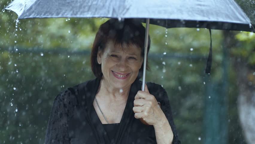 Woman crying under umbrella at rain