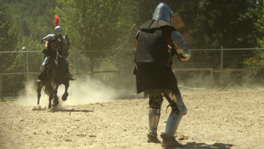 Knight rider on horseback spearing medieval armored warrior with jousting spear