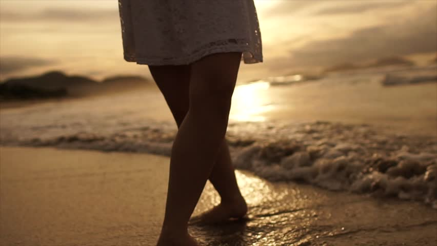 Beautiful scene of a woman walking on ocean beach at sunset #28142002