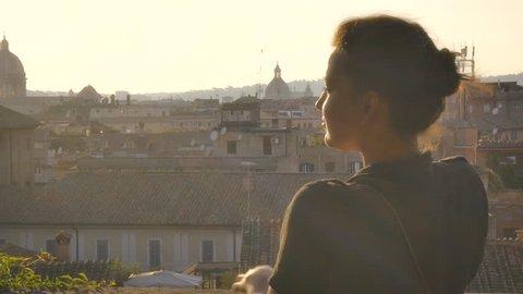 Young woman in campidoglio balcony admires rome's cityscape