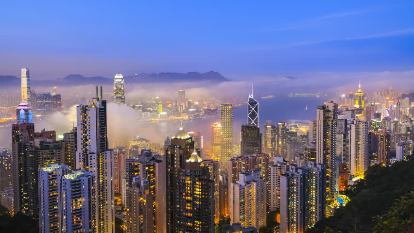 Time lapse Hong Kong skyline from famous Peak View at night. Fog rushing into the city.