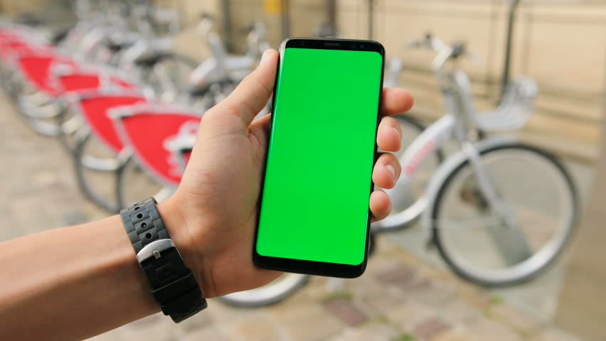 Male Hands Holding Black Smartphone With Green Screen On City