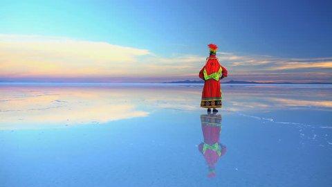 Latin American female in Bolivian National traditional dress on Salar de Uyuni mineral Salt flats at sunrise South America