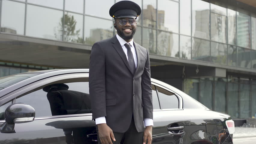 Attentive taxi driver politely opening car door, inviting client to sit down. Smiling afro-american chauffeur near luxury automobile, client assistance, prestige wealth. Driving job, hospitality