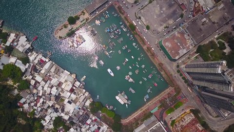 Tsau Wan typhoon shelter at east end of Victoria Harbour, between urban area and construction ground, and slums from another side, aerial shot. Camera look straight down from height, sun light glisten