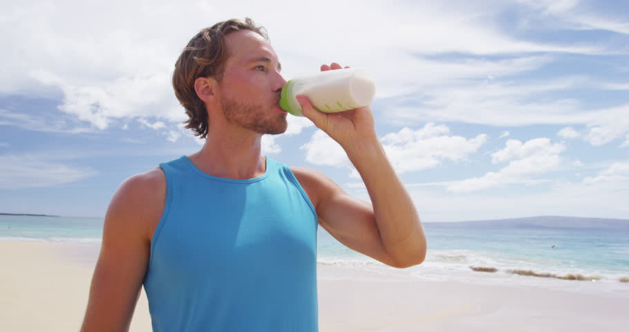 Man drinking protein drink after shaking sports bottle with protein powder mix outside on beach.