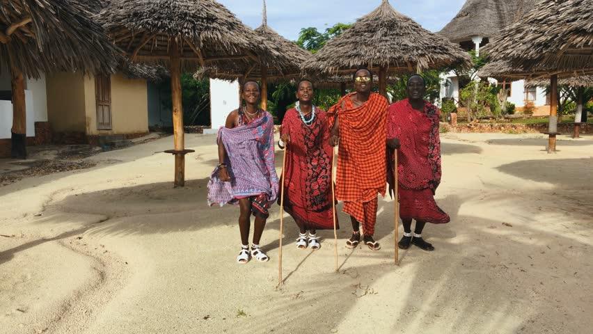 The Masai tribe dances their national African dance on the Indian Ocean beach at sunset and bids farewell to the sun. Tanzania. Zanzibar. 4K.