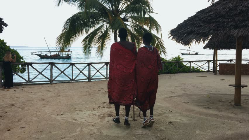 Two Masai people dances their national African dance on the Indian Ocean beach at sunset and bids farewell to the sun. Tanzania. Zanzibar. Slow motion. 4K.