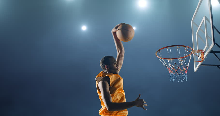 Close up image of professional basketball player making slam dunk during basketball game in floodlight basketball court. The player is wearing unbranded sport clothes. | Shutterstock HD Video #28198921