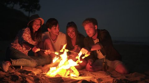 Young cheerful friends sitting by the fire on the beach in the evening, cooking marshmallow on sticks together. Shot in 4k