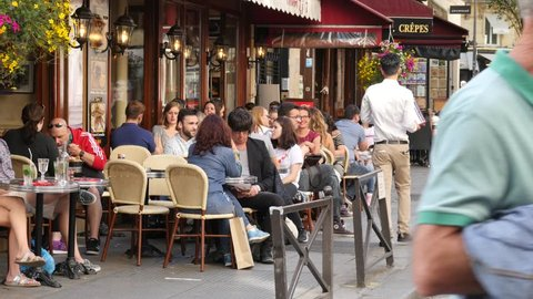 PARIS, FRANCE - MAY 23, 2017: People Sit In Restaurant Eating And Drinking On Cozy Street Of Paris Latin Quarter