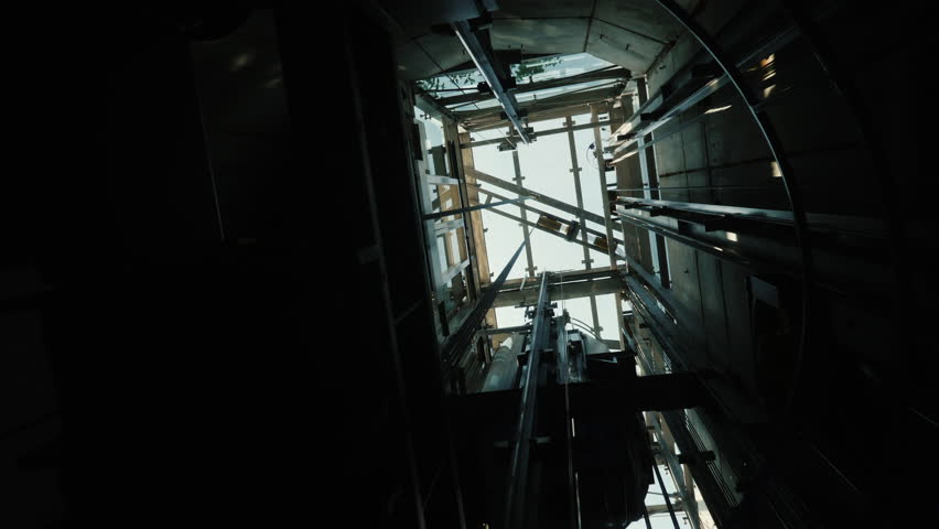 The elevator goes down in the shaft. At the top, you can see the mechanism of the lift, the cables and the blue sky