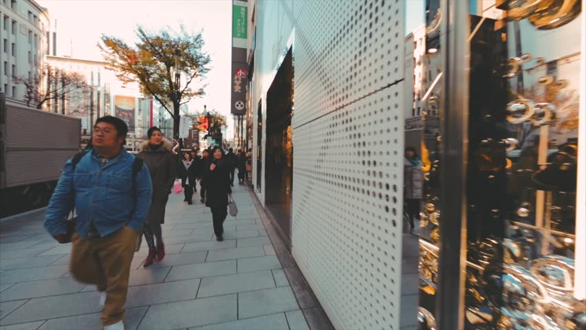 TOKYO, JAPAN - DECEMBER 10, 2016: Walking along the street. Luxury Dior store is on the right. It sells designer fashion accessories, jewelry, fragrance, makeup products