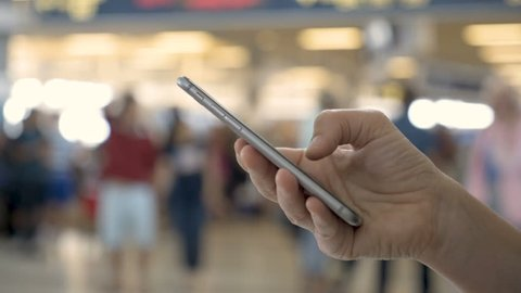Airport traveler using cell phone in busy airport terminal