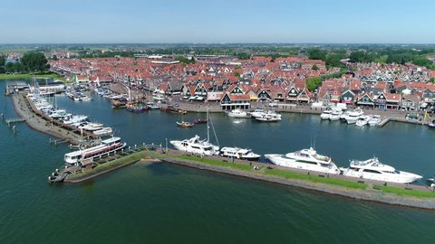 Aerial bird view footage moving right in front of Volendam small fishing town showing tourist boat moving into recreational harbor on left and houses in background popular Dutch tourist attraction 4k