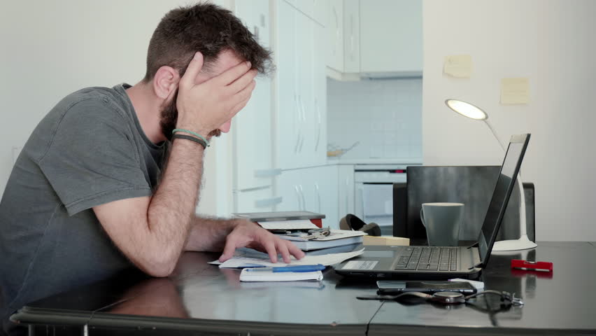 Young man overwhelmed by his bills at home.A young man at home calculates his living expenses and sums his bills and his overdue notices and falls into despair   Shutterstock HD Video #28294951