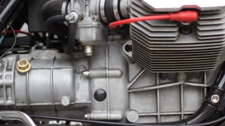 close up detail of motorcycle engine with red wire