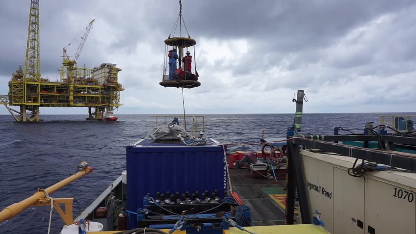 SARAWAK, MALAYSIA - JUNE 12th, 2017: Unidentified workers using personal transfer basket during crews change with background of offshore drilling platform at South China Sea, Malaysia.