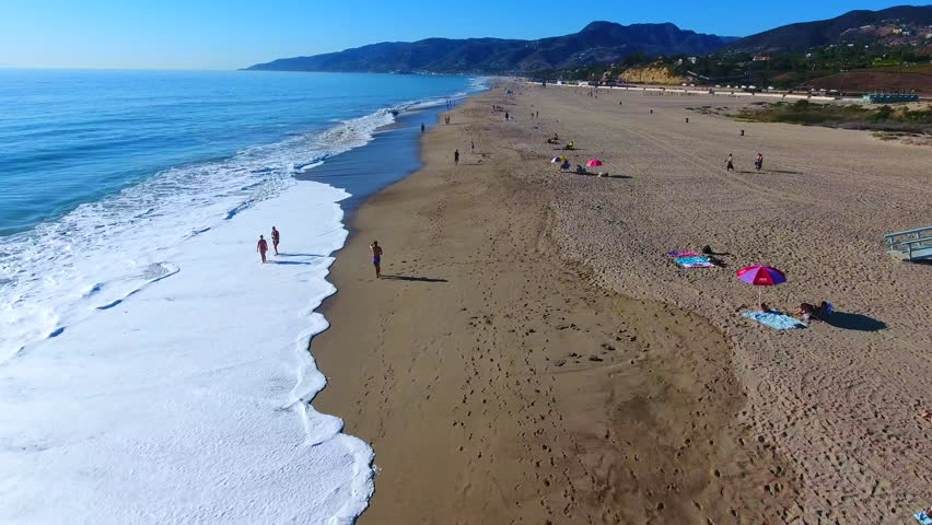 Exciting low flying aerial drone footage of vacationing tourists, waves and sunshine on the beautiful shores of landmark Malibu, California. Terrific 4K aerial clips for b-roll, titles, marketing...