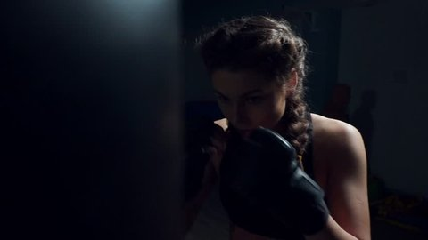 Beautiful young woman punching bag in dark fitness studio. Boxing in slowmotion.