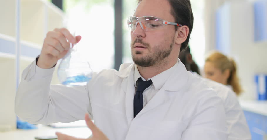 Male Scientist Analyzing Smell Of Liquid In Flask Working In Chemical Laboratory Wear White Coat And Protective Glasses Slow Motion 60 | Shutterstock HD Video #28376302