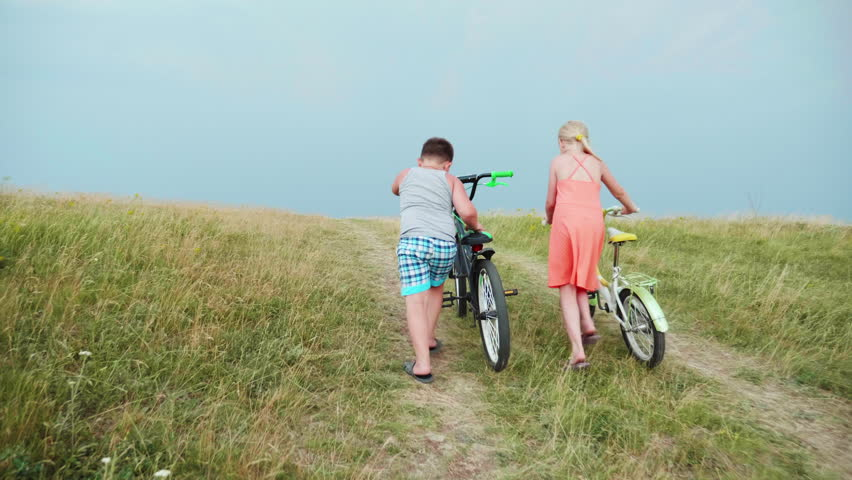 Two small children - a boy and a girl are driving bicycles up the hill, lightning flashes in the distance. The concept is to overcome problems, achieve | Shutterstock HD Video #28376692