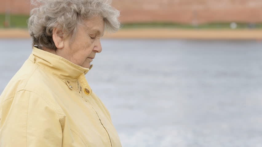 Black wristband. Outdoors a old woman, aged 80s, dressed in a yellow jacket, looks at the results of physical activity using a wristband fitness tracker outdoors.