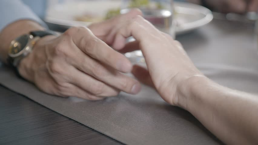 Hands of lovers: a man's hand on top of a woman's, gently holds, strokes her. Close-up. Concept of romance, love, tenderness. Men's hands with a clock stroked a woman's hand with a neat manicure. | Shutterstock HD Video #28393762