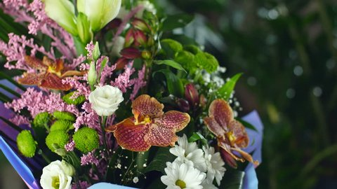 close-up, Flower bouquet in the rays of light, rotation, the floral composition consists of Orchid vanda, Chrysanthemum bacardi, solidago, Eustoma, Alstroemeria, Santini , gypsophila, Russus , Phoenix
