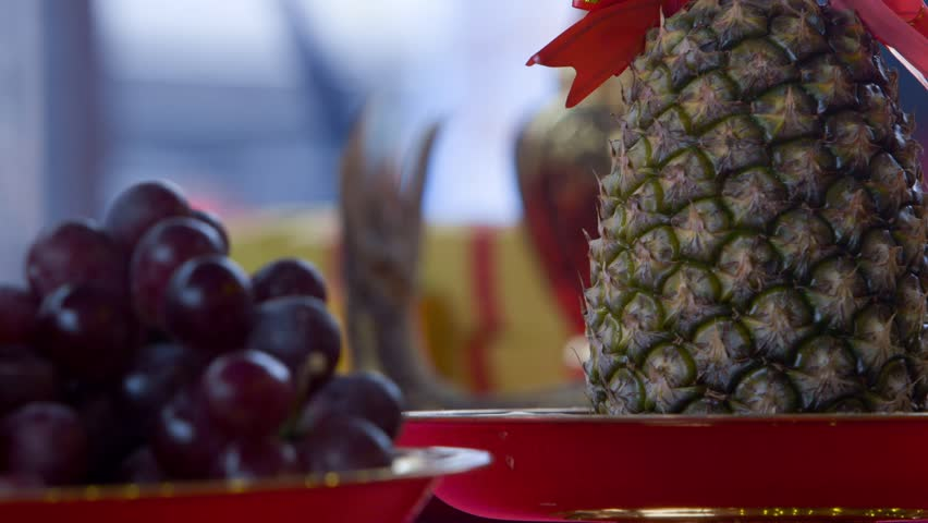 Offering of pineapple, grapes and fruits to the deities in a Chinese temple in Taipei, Taiwan. Offerings to the Gods and Goddesses.