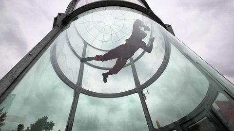 Woman skydiver in an indoor arena ,slow motion. Indoor skydiving wind tunnel.