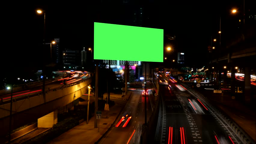 Blank advertising green screen beside road with traffic at night, for advertisement, time lapse.
