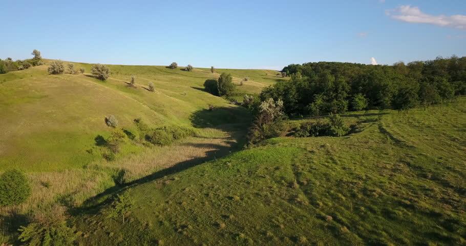 Aerial: Flight over a green grassy hills, beautiful nature   Shutterstock HD Video #28449022