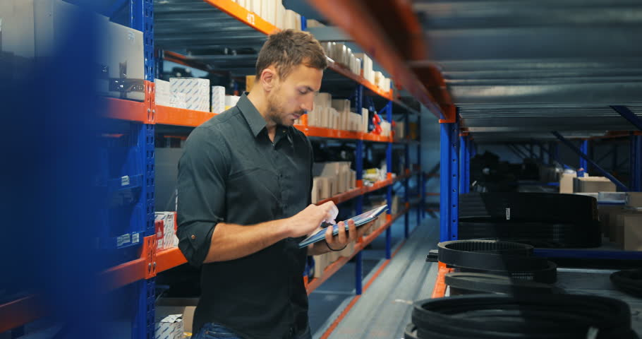 Man in a warehouse is checking inventory levels of goods, using his tablet, Last in last out, First in first out concept photo, orange-blue perspective background | Shutterstock HD Video #28457641