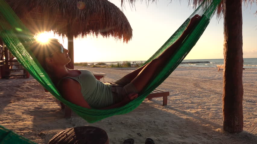 SLOW MOTION Happy young woman on vacation laying and resting in hammock at golden sunset in hot summer on Mexico beach. Serene woman relaxing in swinging hammock on sandy beach at sunrise golden light