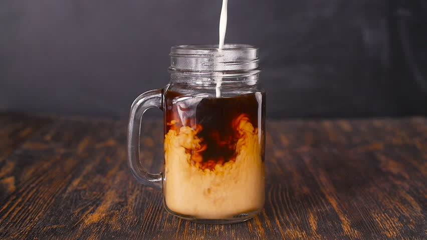 Milk is poured into coffee