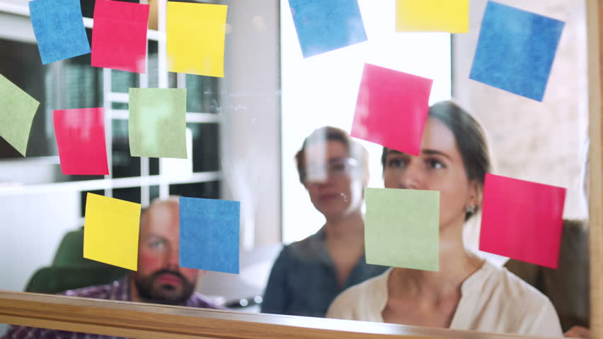 Team of young managers and workers look on sticker on glass during business meeting and work discuss in office space | Shutterstock HD Video #28507462