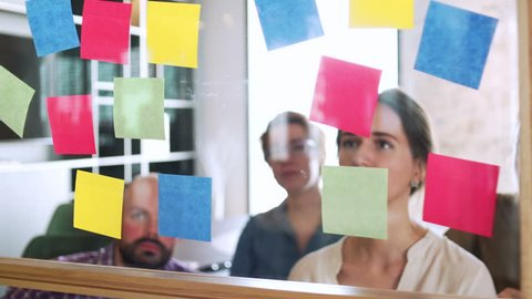 team of young managers and workers look on sticker on glass during business meeting and work discuss in office space