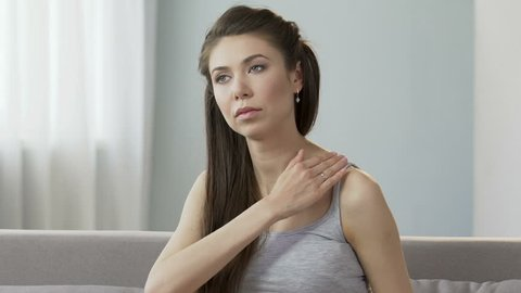 Young female massaging neck and shoulders, releasing disturbing pain, stiff neck